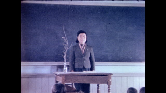 / children seated at desks / teacher giving instruction / children standup and bow to their teacher school children in post war japan on january 18... - 1946年点の映像素材/bロール