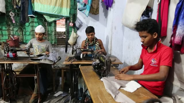 children seen inside bangladesh's garments workshop in dhaka children as young as nine have been found working shift up to 18 hours long inside... - macchina per cucire video stock e b–roll