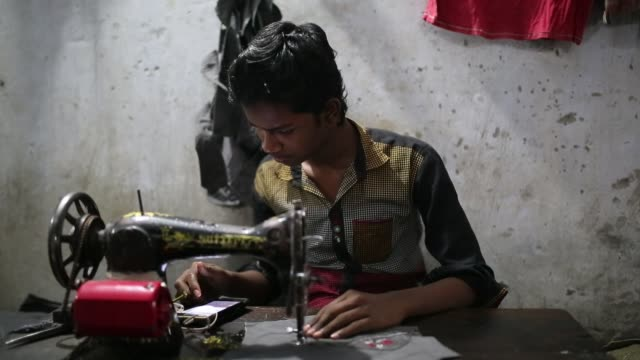 stockvideo's en b-roll-footage met children seen inside bangladesh's garments workshop in dhaka children as young as nine have been found working shift up to 18 hours long inside... - werkgelegenheid en arbeid