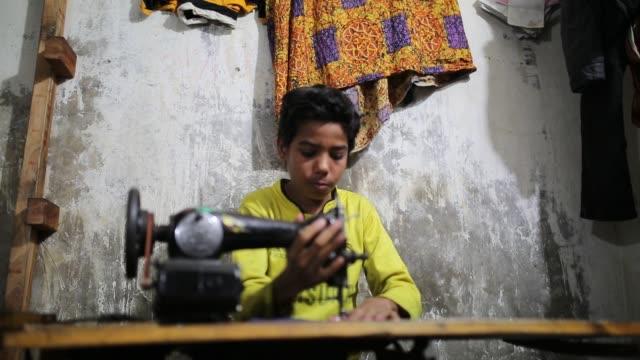 vídeos de stock, filmes e b-roll de children seen inside bangladesh's garments workshop in dhaka children as young as nine have been found working shift up to 18 hours long inside... - escravidão