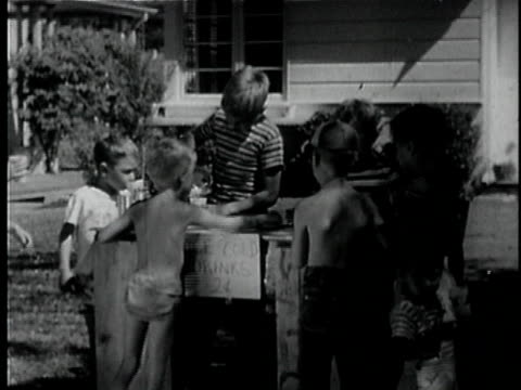 b/w ms children selling and pouring cold drinks at sidewalk stand / los angeles, california, usa - ausgusstülle stock-videos und b-roll-filmmaterial