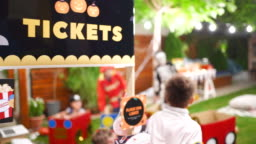 Children selling tickets from ticket stand to their friends at drive-in movie party