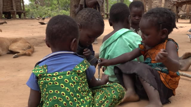 children sharing bowl of porridge in drought hit zambia where the lack of rain means food is in very short supply - hungrig stock-videos und b-roll-filmmaterial