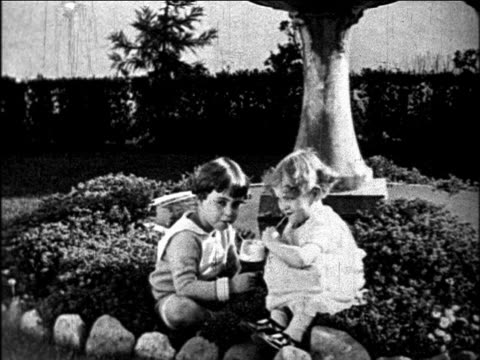B/W 1927 2 children sharing drink with 2 straws / one kisses other / educational