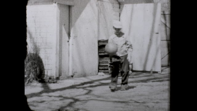 vidéos et rushes de children shooting basketball through the hoop; boy dribbling the ball while walking toward camera; other houses and trees in the background - panier de basket