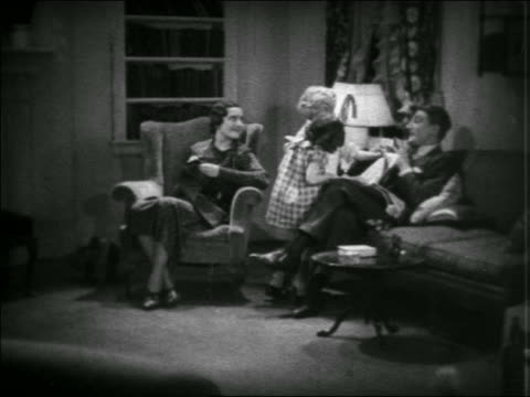 vidéos et rushes de b/w 1935 children showing newspaper to mother + father reading in living room / educational - journal