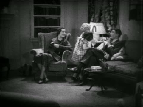 vídeos y material grabado en eventos de stock de b/w 1935 children showing newspaper to mother + father reading in living room / educational - 1935