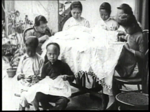 1932 montage children sitting and sewing a blanket together with woman and two boys working at a table / china  - 1932 stock videos & royalty-free footage