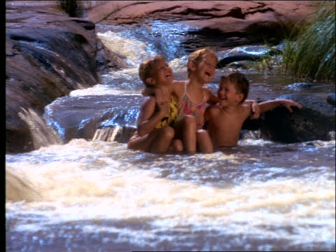 3 children sitting arm in arm in stream + laughing - swimming costume stock videos & royalty-free footage