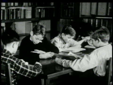 vídeos y material grabado en eventos de stock de 1946 montage children sitting around tables writing and reading books in a library / new york, new york, united states  - blanco y negro