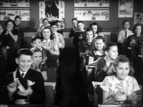 B/W 1938 children sitting at desks in classroom applauding at offscreen dog + policeman