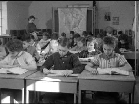 vidéos et rushes de children sitting at desks reading silently from open text books female teacher standing in back of classroom mounted map of united states pulled down... - enseignante