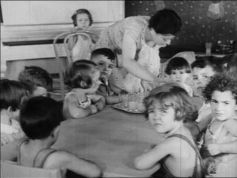 b/w 1934 children sitting at table being served snack in nursery school / wpa project / newsreel - anno 1934 video stock e b–roll