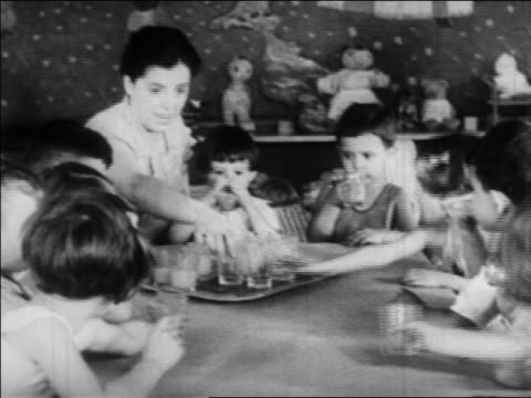 vidéos et rushes de b/w 1934 children sitting at table drinking juice in nursery school / wpa project / newsreel - enseignante