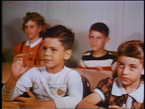 1953 children sitting at tables raising hands in classroom / educational