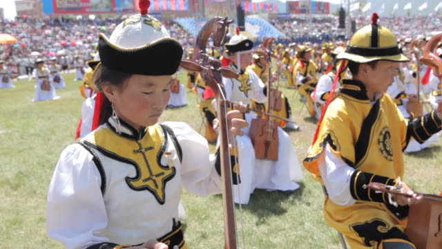 children sitting in the middle of stadium and playing string instrument called morin khuur - string instrument stock videos and b-roll footage