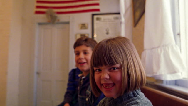 MS PORTRAIT 3 children sitting on bench in schoolhouse goofing off + laughing / American flag in background