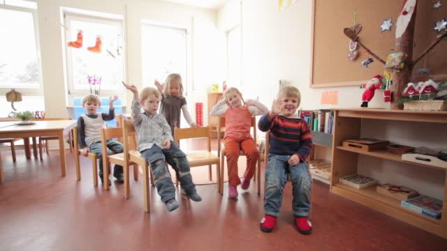 ms children sitting on chairs and waving / potsdam, brandenburg, germany - nursery school building stock videos & royalty-free footage