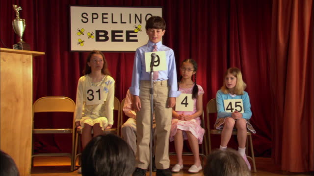 Children sitting on stage in spelling bee / boy walking up to microphone and spelling word / next boy up misspelling word / Los Angeles, California