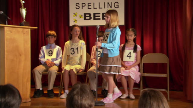 Children sitting on stage in spelling bee / girl walking up to microphone and spelling word / Los Angeles, California