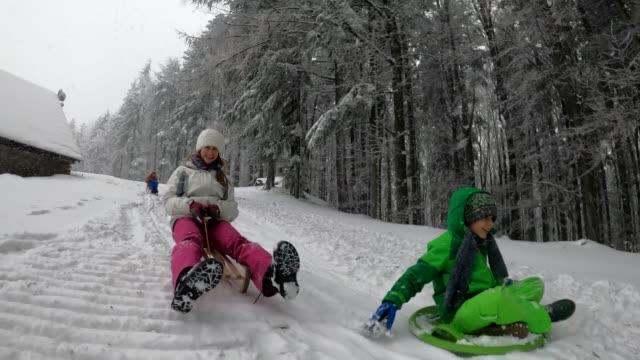 vídeos y material grabado en eventos de stock de niños en trineo en el bosque de invierno. - tobogan