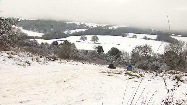 children sledging down hill in surrey over snowfall - hill stock videos & royalty-free footage