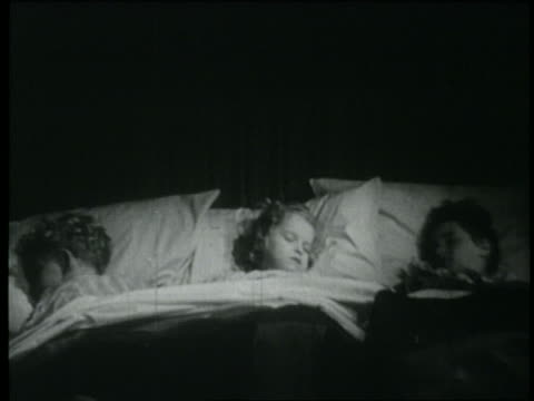 vidéos et rushes de b/w 1946 3 children sleeping in large bed - frère