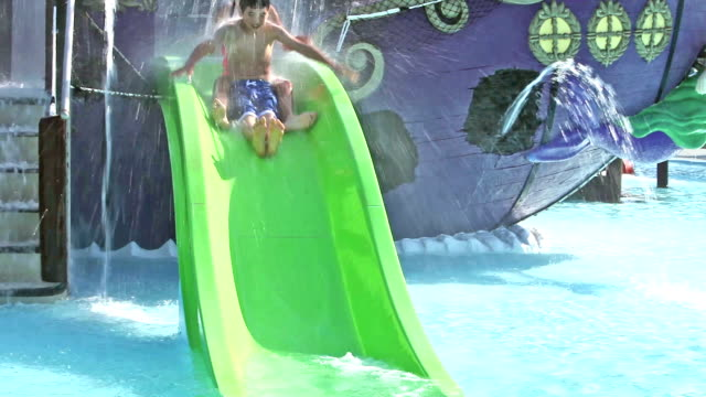 Children sliding down at waterslide together