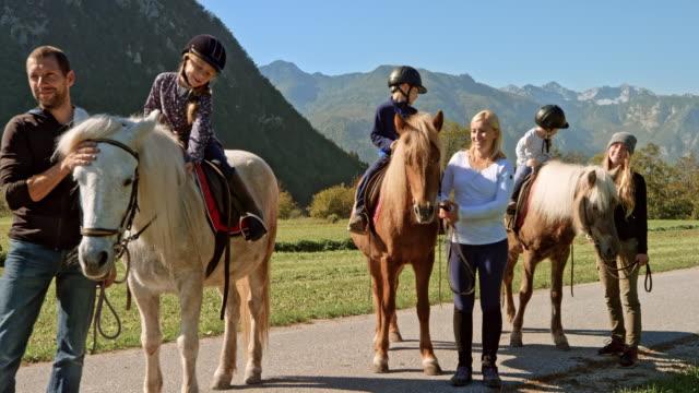 kinder lächeln beim sitzen auf ihren pferden stehen noch im sonnenschein - verantwortung stock-videos und b-roll-filmmaterial