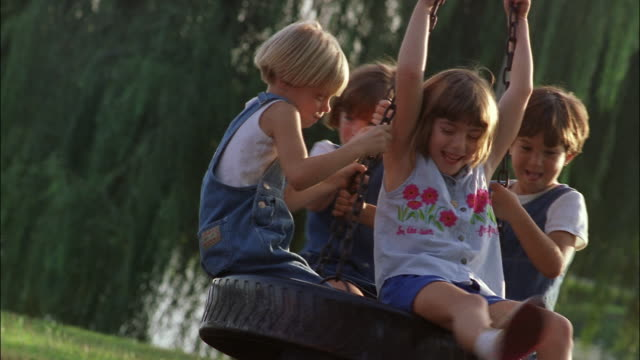 children spin on a tire swing. - tire swing stock videos & royalty-free footage