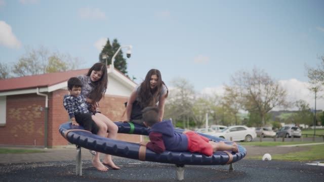 children spinning on playground equipment at a park - rotorua stock videos and b-roll footage