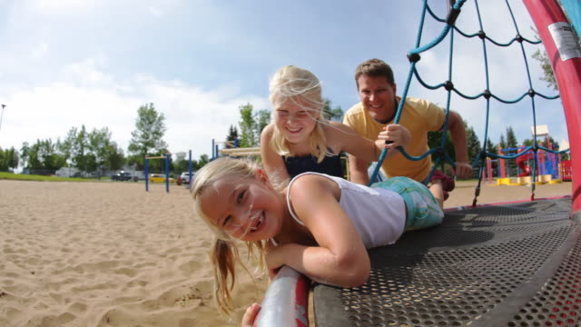 stockvideo's en b-roll-footage met children spinning on ride at playground - speeltuin