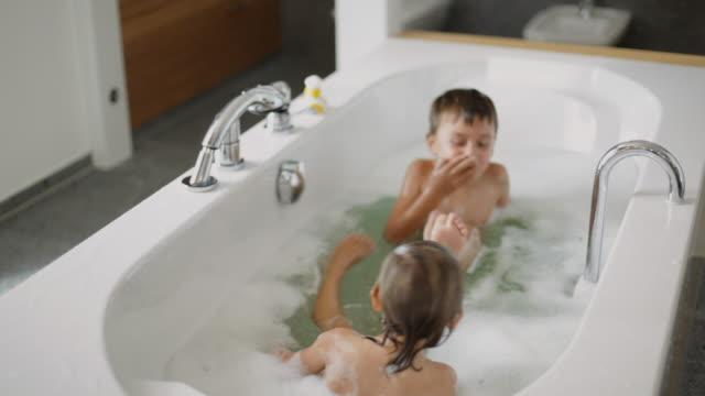 ms zi children (2-5) splashing in bathtub / kleinmachnow, brandenburg, germany - bath stock videos & royalty-free footage