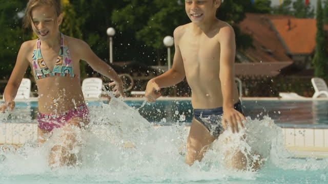 hd slow motion: children splashing in pool - pre adolescent child stock videos and b-roll footage