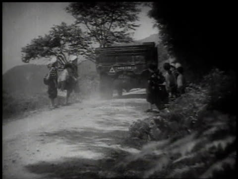 1939distant children standing along dirt road when a truck stops and the children get in / japan - 1930~1939年点の映像素材/bロール