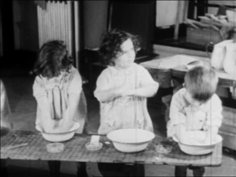 b/w 1934 3 children standing at basins washing themselves at nursery school / wpa project / newsreel - anno 1934 video stock e b–roll