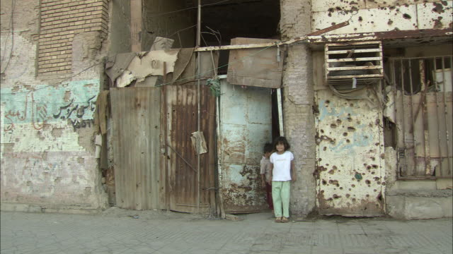 ws pan children standing at door of building with many bullet holes / khorramshahr, khuzestan province, iran - iran stock videos & royalty-free footage