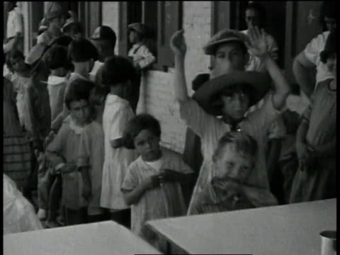 children standing in line for milk which they drink out of tin cups / baton rouge louisiana united states - baton rouge stock-videos und b-roll-filmmaterial