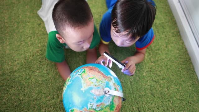 stockvideo's en b-roll-footage met kinderen bestudeert een wereldbol - vergrootglas