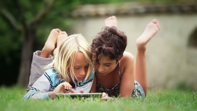 vídeos y material grabado en eventos de stock de los niños estudian y jugando en un comprimido - tumbado boca abajo