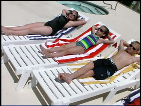 vídeos de stock e filmes b-roll de children sunbathing - encostado
