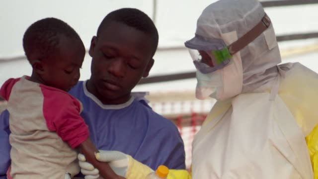 vídeos de stock, filmes e b-roll de children suspected of having ebola being cared for at treatment centre by people that have already survived the disease beni demcratic republic of... - ébola