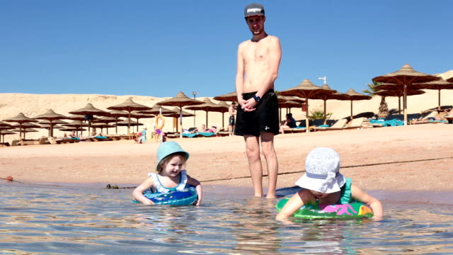 kinder schwimmen im meer nahe dem ufer. vater betreut kinder. - rotes meer stock-videos und b-roll-filmmaterial