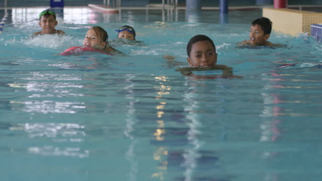 children swimming in a pool at a fitness centre - swimming stock videos & royalty-free footage