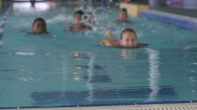 children swimming in a pool at a fitness centre - indoors stock videos & royalty-free footage
