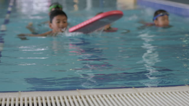 Kinder, die schwimmen in einem Pool an ein Fitness-Center