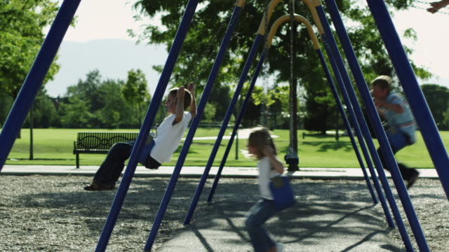 ws pan slo mo children (4-13) swinging on swings in park / orem, utah, usa - swinging stock videos & royalty-free footage