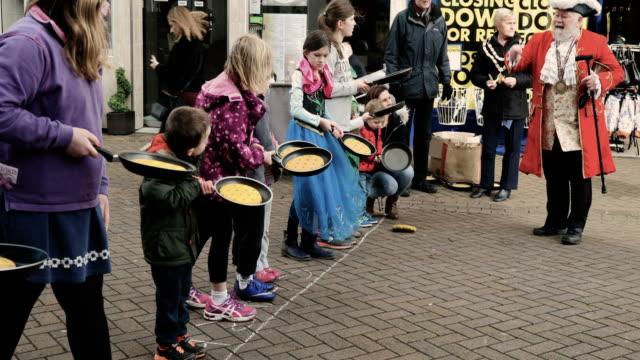 vidéos et rushes de children take place annual shrove tuesday pancake race in fore street on on february 28, 2017 in trowbridge, england. - mardi gras fête religieuse