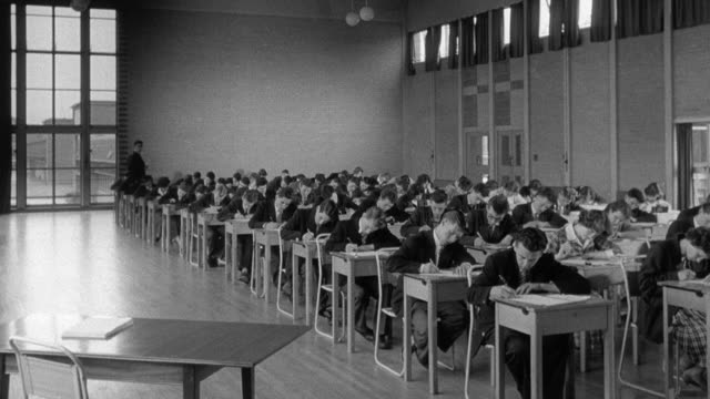 1960 montage children taking gce test in classroom / united kingdom - 試験点の映像素材/bロール