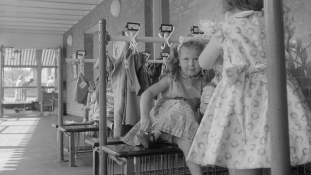 1960 MONTAGE Children taking off shoes and hanging coat on hook at nursery school / United Kingdom